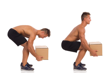 injury: Young fit man showing how to pick up a heavy carton box. Side view. Full length studio shot isolated on white.