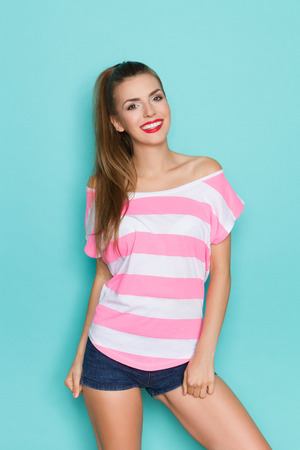 Young woman in pink striped shirt and jeans shorts posing. Three quarter length studio shot on teal background.