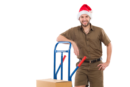 leaning on the truck: Happy delivery man in santa claus hat lean on a delivery cart and looking at camera. Three quarter length studio shot isolated on white Stock Photo