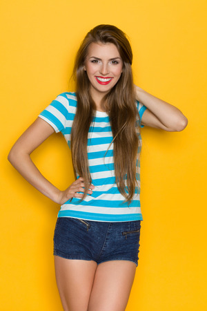 three quarter length: Beautiful young woman in turquoise striped shirt posing with hand on hip. Three quarter length studio shot on yellow background. Stock Photo