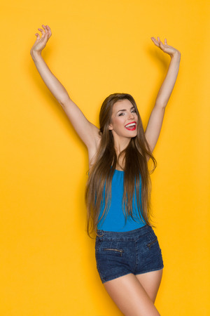 shouting: Shouting young woman in blue shirt and jeans shorts posing with arms raised. Three quarter length studio shot on yellow background.