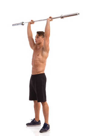 legs apart: Muscular man holding a barbell over his head. Side view. Full length studio shot isolated on white.