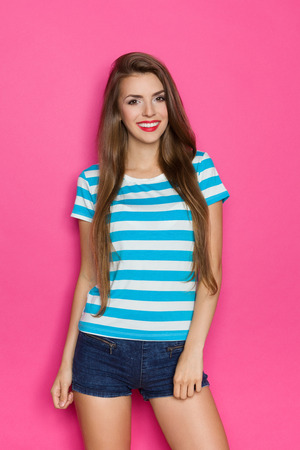 Beautiful young woman in stripped shirt and jeans shorts posing against pink wall.