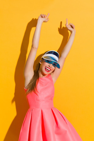 three quarter length: Shouting young woman in pink dress and sun visor pointing with arms raised. Three quarter length studio shot against yellow background.