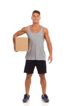 서 그의 팔에서 판지 상자를 들고 검은 색 반바지와 운동화 젊은 남자. 전체 길이 스튜디오 샷 화이트에 격리입니다.