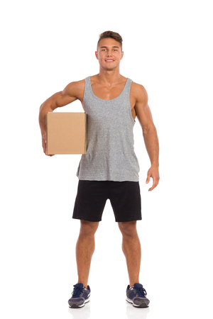 Young man in black shorts and sneakers standing and holding cardboard box under his arm. Full length studio shot isolated on white.