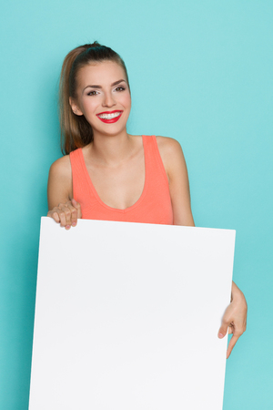 three quarter: Smiling young woman in orange shirt holding white copy space. Three quarter length studio shot on turquoise background.