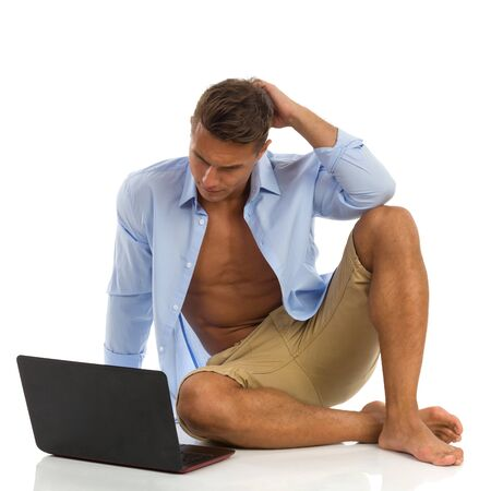 unbuttoned: Young man in blue unbuttoned shirt and shorts, sitting on a floor, working on a laptop and thinking. Full length studio shot isolated on white.