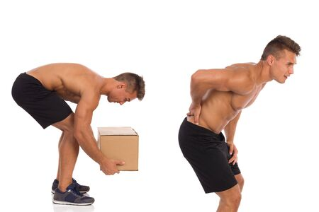stretching condition: Young muscular man picking up heavy box and holding lower back in pain. Studio shot isolated on white. Stock Photo