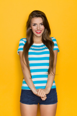 three quarter length: Beautiful young woman in turquoise striped shirt posing against yellow wall. Three quarter length studio shot.