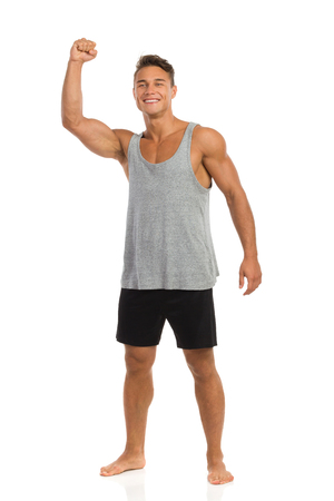 barefoot: Happy muscular man in sport outfit standing barefoot and holding fist raised. Full length studio shot isolated on white. Stock Photo