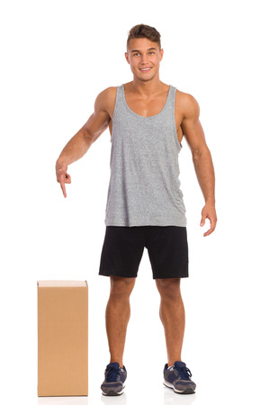 legs apart: Smiling young man in sports clothes standing with legs apart close to carton box and pointing down. Full length studio shot isolated on white.