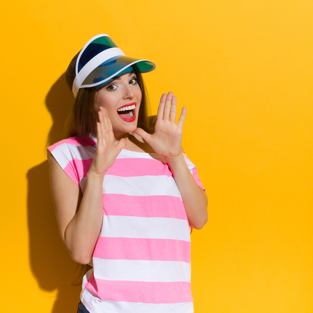 Excited young woman in pink stripped shirt and blue sun visor shouting and holding hands raised. Waist up studio shot on yellow background.