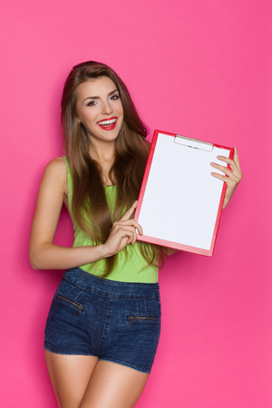 three quarter: Smiling young woman holding clipboard. Three quarter length studio shot on pink background.