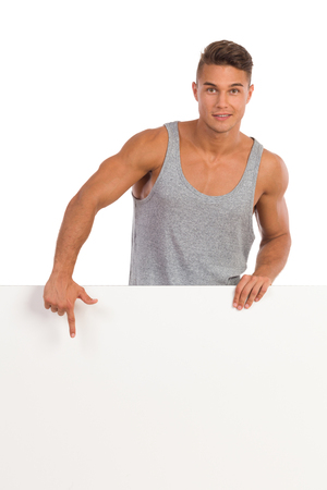 waist shot: Cheerful young man in gray shirt standing behind white banner and pointing. Waist up studio shot isolated on white. Stock Photo