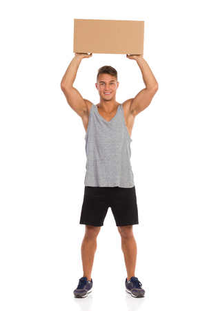 legs apart: Smiling young man in gray shirt, black shorts and sneakers standing with legs apart and holding carton box over his head. Full length studio shot isolated on white.