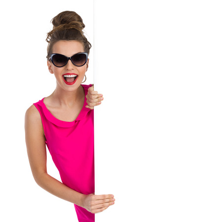 Shouting young woman in sunglasses and hair bun peeking behind big white banner. Waist up studio shot isolated on white. Stockfoto
