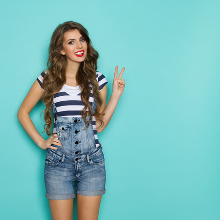 three quarter length: Beautiful smiling young woman in dungarees and blue striped shirt showing victory hand sign. Three quarter length studio shot on teal background.