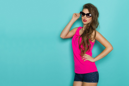 three quarter length: Beautiful girl with long curly hair posing in sunglasses, jeans shorts and pink top. Three quarter length studio shot on teal background.