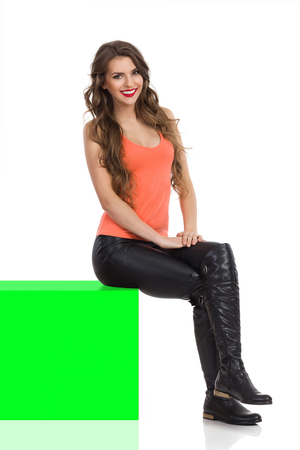key box: Smiling young woman in black leather trousers, orange shirt and boots sitting on green chroma key box and looking at camera. Side view, Full length studio shot isolated on white.