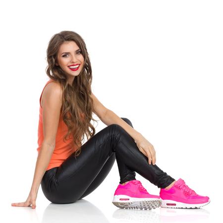 オレンジ色のシャツの若い女性の黒革ズボン、ピンクのスニーカー、床に座って、カメラ目線を笑っています。スタジオ撮影で孤立した白、完全な 写真素材