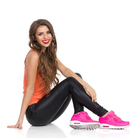 Smiling young woman in orange shirt, black leather trousers, pink sneakers sitting on a floor and looking at camera. Full length, side view, studio shot isolated on white.