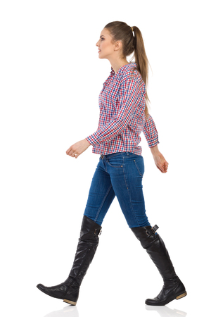 ponytail: Young woman in jeans, black boots and lumberjack shirt walking. Side view, full length studio shot isolated on white. Stock Photo