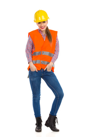 lumberjack shirt: Smiling young woman in orange reflective vest, lumberjack shirt, jeans, black boots, posing in yellow hardhat and holding hands in pockets. Full length studio shot isolated on white.