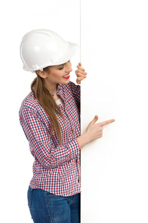 lumberjack shirt: Smiling beautiful young woman in white hardhat and lumberjack shirt standing behind big white banner, pointing and reading. Waist up studio shot isolated on white. Stock Photo
