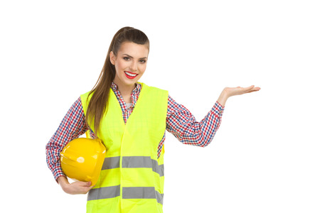 lumberjack shirt: Smiling young woman in reflecive vest holding hard hat under her arm, holdin hand raised and presenting. Waist up studio shot isolated on white.