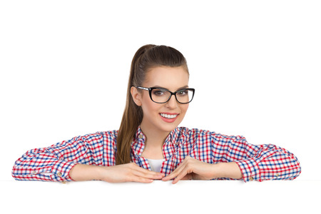 lumberjack shirt: Smiling beautiful smiling young woman in glasses ans lumberjack shirt leans on a white banner and looking at camera. Head and shoulders studio shot isolated on white.