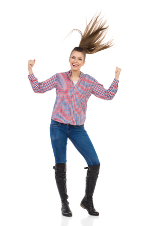 lumberjack shirt: Young woman in jeans, black boots and lumberjack shirt cheering with arms outstretched and throwing hair. Full length studio shot isolated on white.