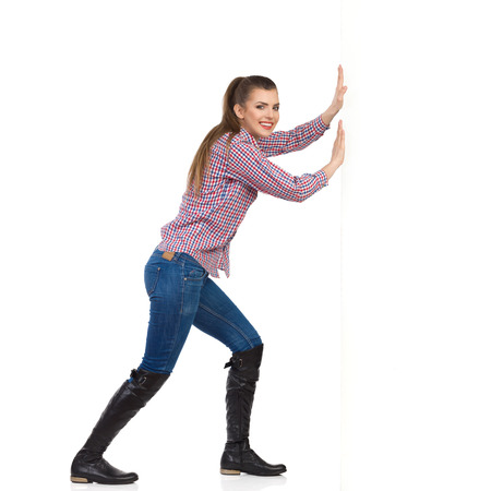 strong women: Smiling young woman in jeans, black boots and lumberjack shirt pushing a white wall and looking at camera. Side view, full length studio shot isolated on white.