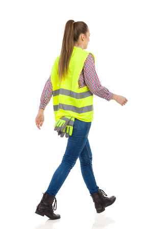 reflective vest: Young woman in green reflective vest, jeans and black boots walking, Rear view. Full length studio shot isolated on white.
