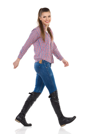 lumberjack shirt: Smiling young woman in jeans, black boots and lumberjack shirt walking and looking at camera. Side view, full length studio shot isolated on white. Stock Photo