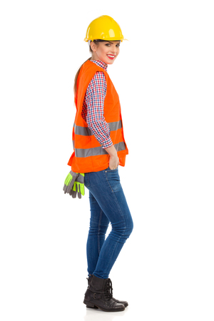reflective vest: Smiling young woman in orange reflective vest, lumberjack shirt, jeans, black boots, posing in yellow hardhat and holding hand in pocket. Side view. Full length studio shot isolated on white.