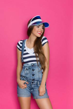 three quarter: Beautiful young woman in striped shirt, jeans dungarees shorts and blue sun visor posing and looking away. Three quarter length studio shot on pink background.