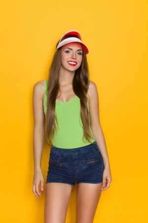 visor: Young woman in green shirt and red sun visor. Three quarter length studio shot on yellow background.