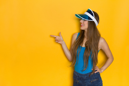 waist shot: Smiling young woman in blue shirt and sun visor pointing at copy space. Waist up studio shot on yellow background. Stock Photo