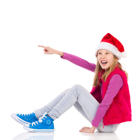 Laughing girl in Santas hat is sitting on a floor looking up and pointing. Full length length studio shot isolated on white. Stock Photo