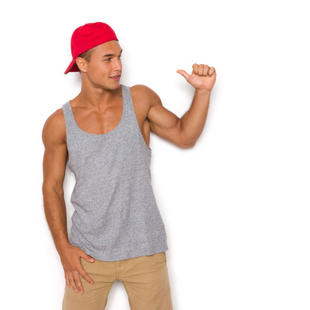 three quarter length: Handsome young man in red cap and gray shirt posing against white wall, showing thumb up and looking away. Three quarter length studio shot on white background Stock Photo