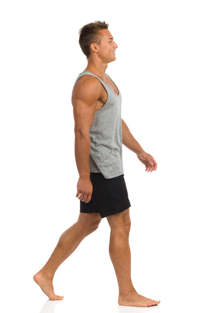 side shot: Young man in black shorts and gray shirt walking barefoot. Side view. Full length studio shot isolated on white.