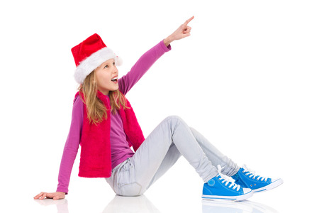 blonde girls: Girl in Santas hat is sitting on a floor looking up and pointing. Full length length studio shot isolated on white.