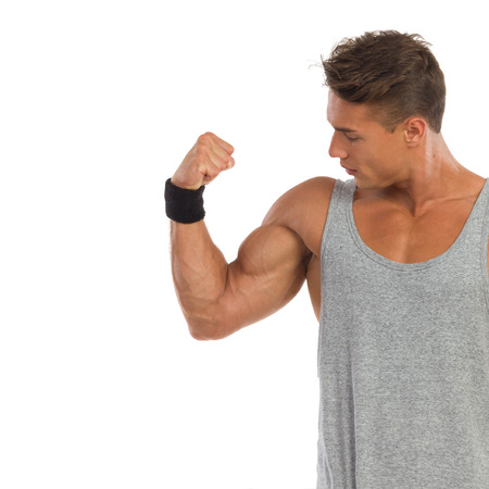waist shot: Young man in gray shirt flexing biceps and looks at it. Waist up studio shot isolated on white.