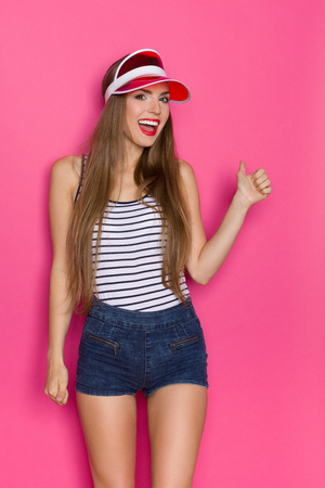 visor: Smiling young woman in striped shirt and red sun visor showing thumb up. Three quarter length studio shot on pink background.