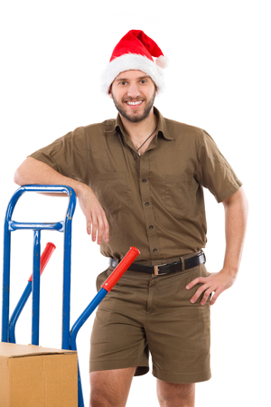 leaning on the truck: Smiling delivery man in santa claus hat lean on a delivery cart and looking at camera. Three quarter length studio shot isolated on white. Stock Photo