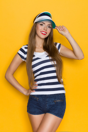 three quarter length: Beautiful young woman in blue striped shirt, jeans shorts and plastic sun visor posing with hand on hip. Three quarter length studio shot on yellow background. Stock Photo