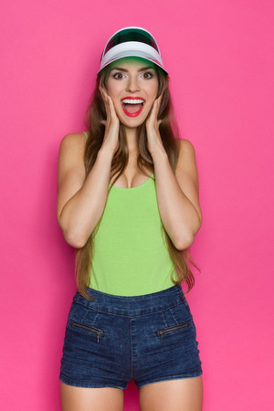three quarter length: Shocked young woman in lime green shirt and green sun visor holding hands on chin. Three quarter length studio shot on pink background.