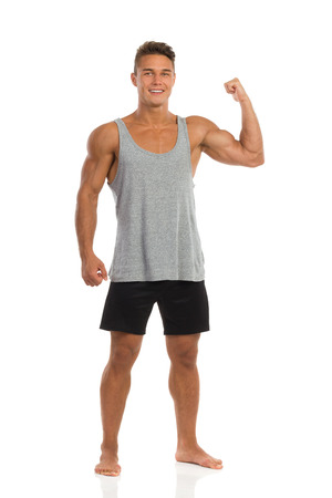 legs apart: Young man in black shorts and gray shirt standing barefoot, flexing biceps and looking at camera. Full length studio shot isolated on white.
