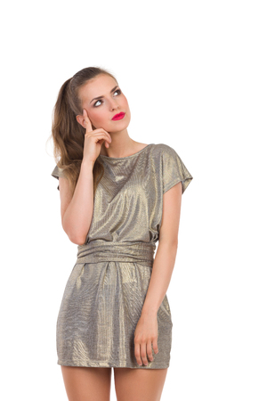 three quarter: Beautiful young woman in gold mini dress thinking and looking away. Three quarter length studio shot isolated on white. Stock Photo